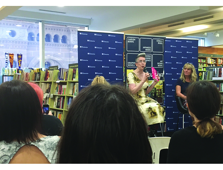 in the background there are many shelves of books, in the forground you can see the back of peoples' heads. In the middle, you can see two white women seated in front of a Kinokunyia banner, one is holding up a copy of the book Summer Skin