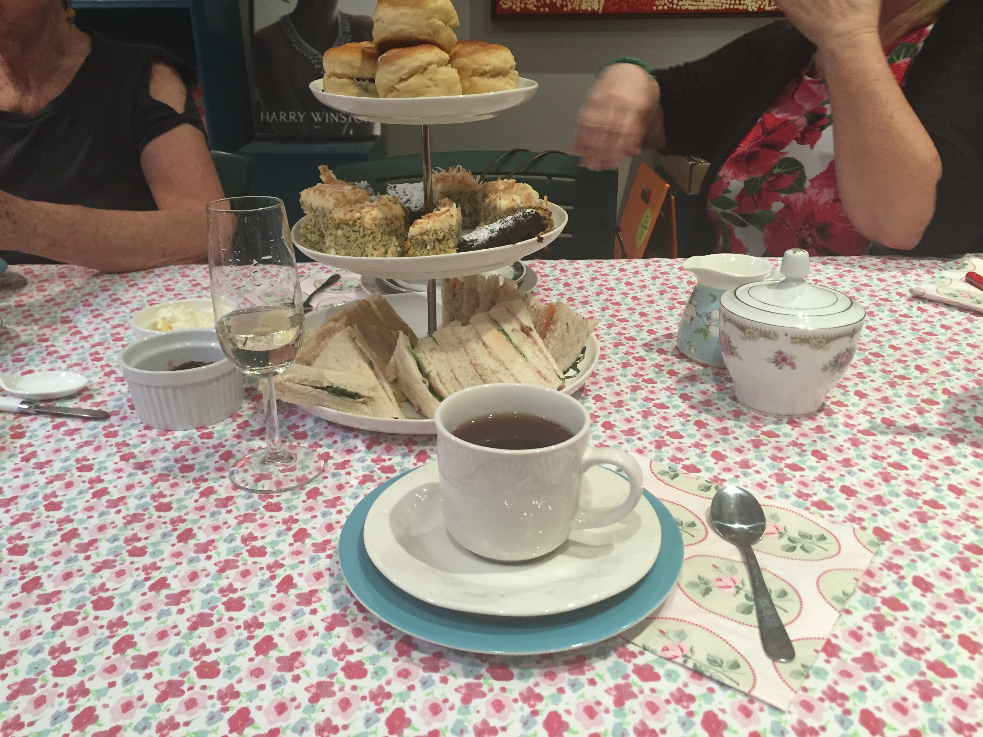 Photograph of a table with a cup of tea in a saucer in front of a three tier cake stand with high tea: cakes, scones and sandwiches