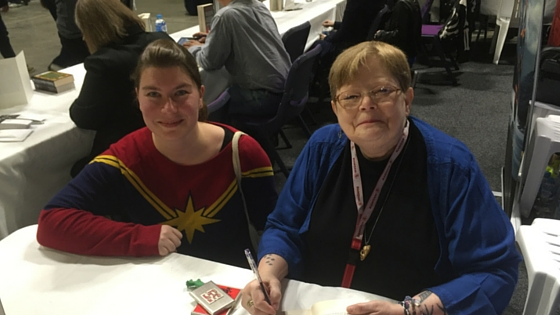 Photo with Tamora Pierce. Shows two white women behind a table, one has brown hair and is wearing a red, and blue Captain Marvel jumper. One has short blondish hair and glasses and is wearing blue. She is holding pen to sign books.