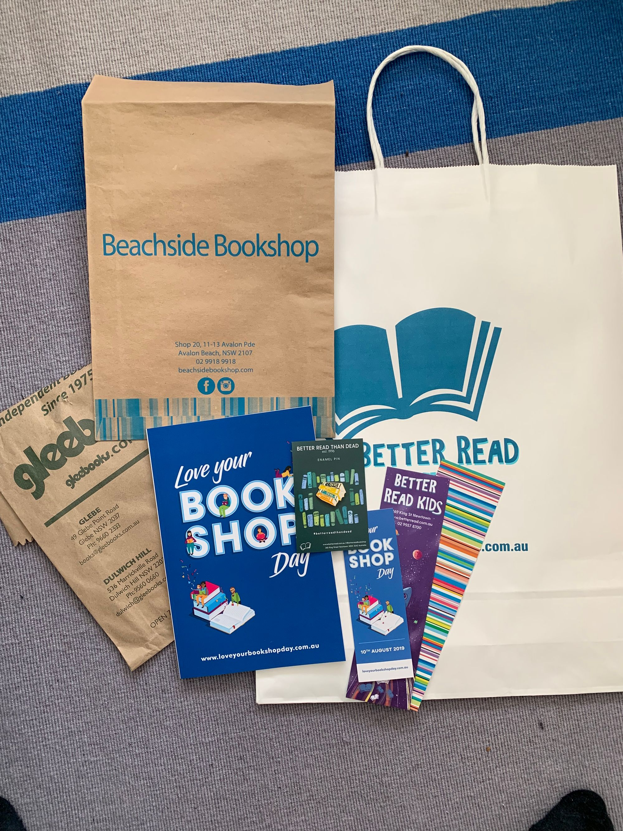 Photo of three bookstore paper bags, a love your bookshop day notebook, three bookshop branded bookmarks and a Better Read Than Dead enamel pin